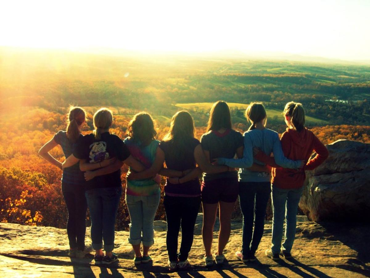 group of women standing together on top of a mountain