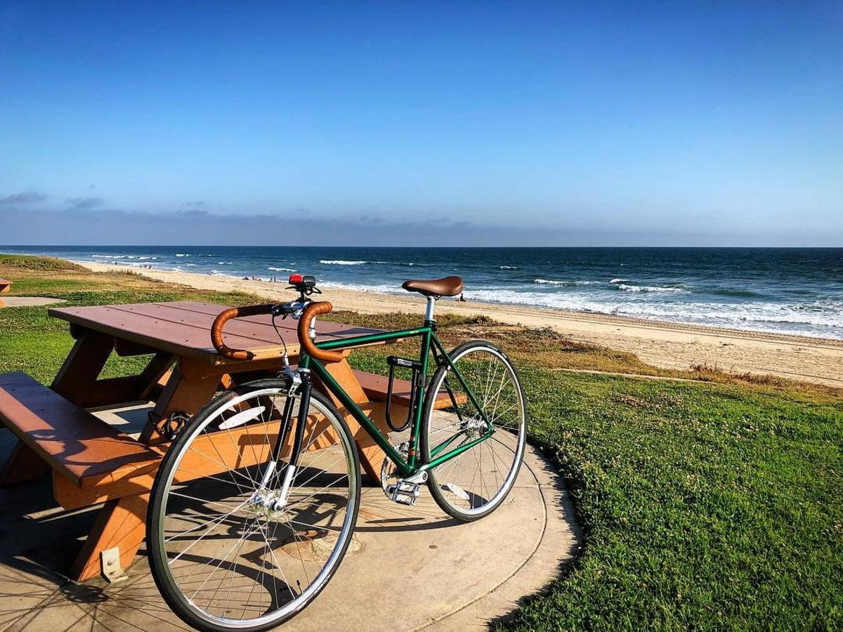 Bike leaning against a picnic table by the beach in Huntington Beach