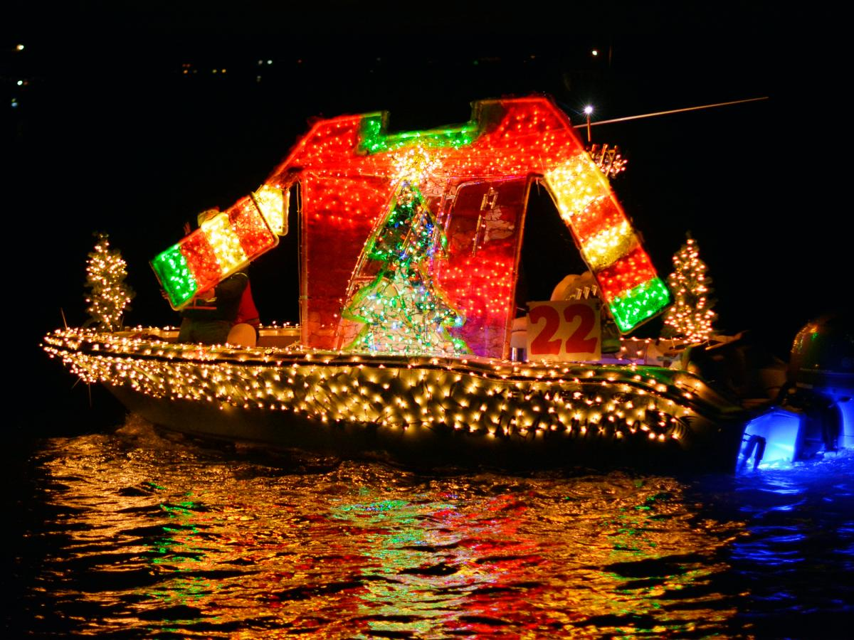 Boat covered in Christmas lights out in the water at the NC Holiday Flotilla