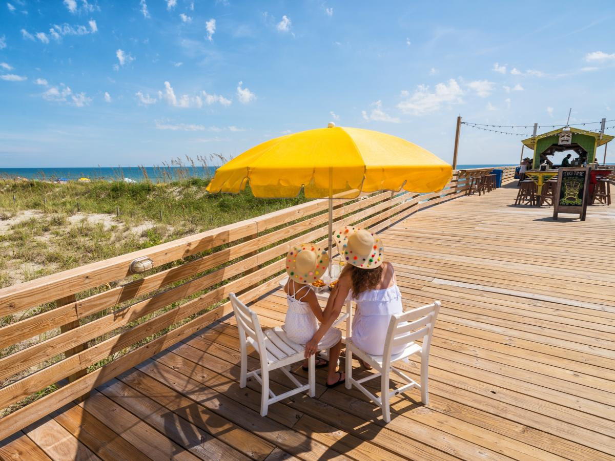 Mother and daughter enjoy the view of Carolina Beach from a patio