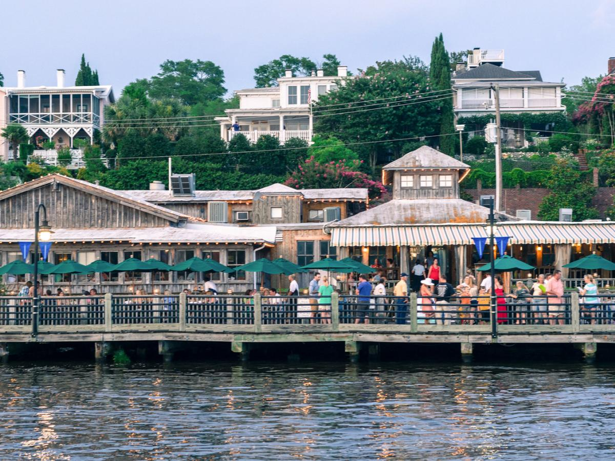 Shops and restaurants with patrons dining along the Wilmington Riverwalk