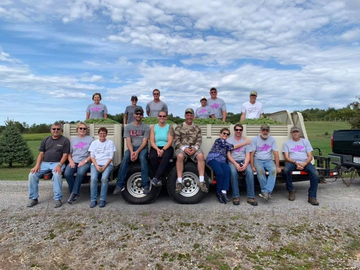 Group of grape harvest participants sitting on a truck at Rock Ridge Vineyards in the Stevens Point Area
