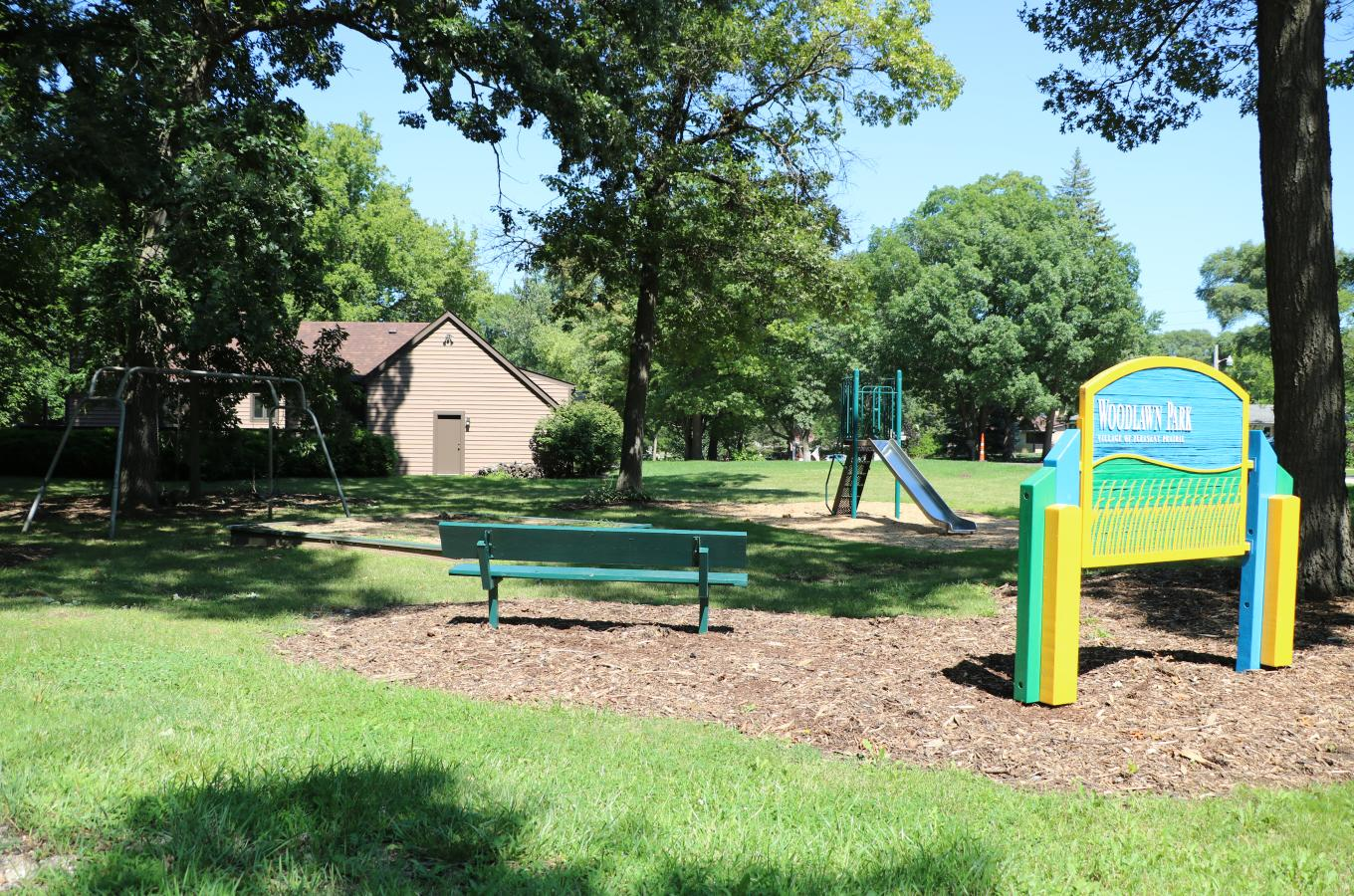 Woodlawn Park Sign with playground equipment in back V Pic