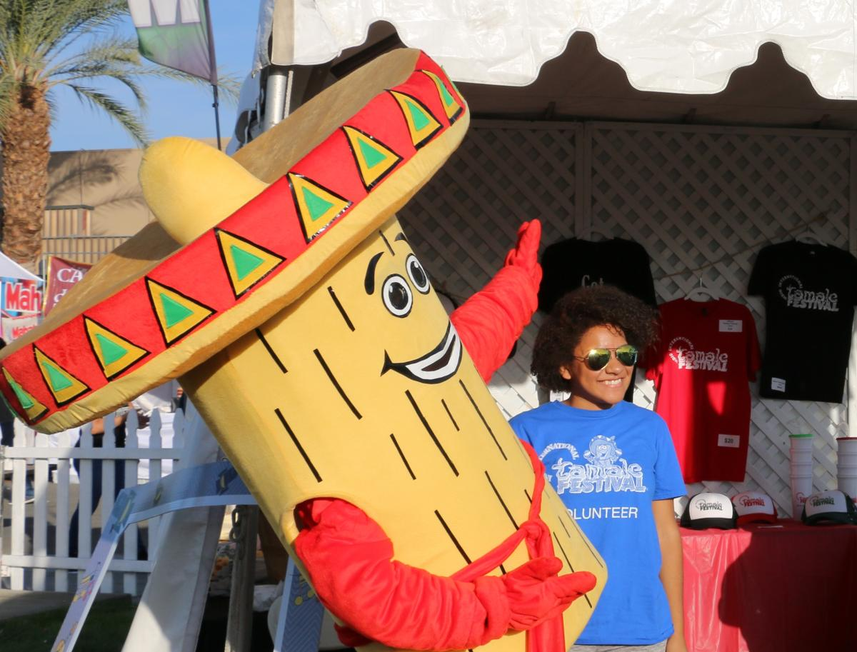 A volunteer at the Indio International Tamale Festival with the Festival Mascot