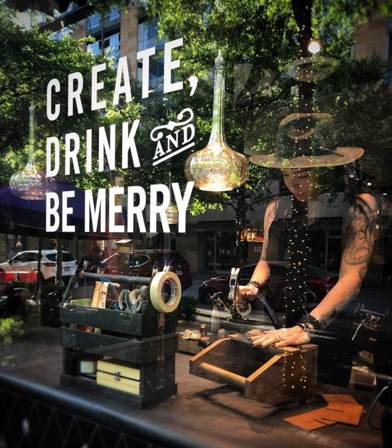 maker at Upstairs Circus working behind window that says Create Drink and Be Merry