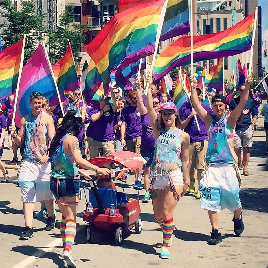 A group of young people holding rainbow flags in the Cincinnati Pride parade