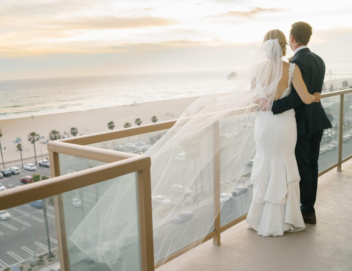 Newlyweds gazing at the ocean from a balcony at the Waterfront Beach Resort in Huntington Beach