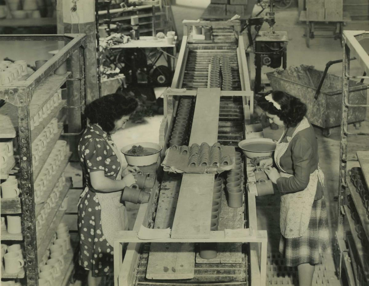 Two women work on factory line putting handles on mugs at Victor Insulators