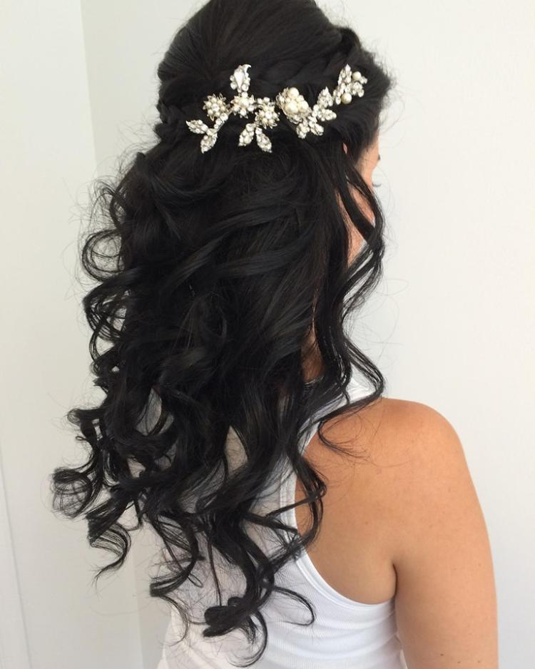 A woman stands with long black curls and a crown of flowers and pearls