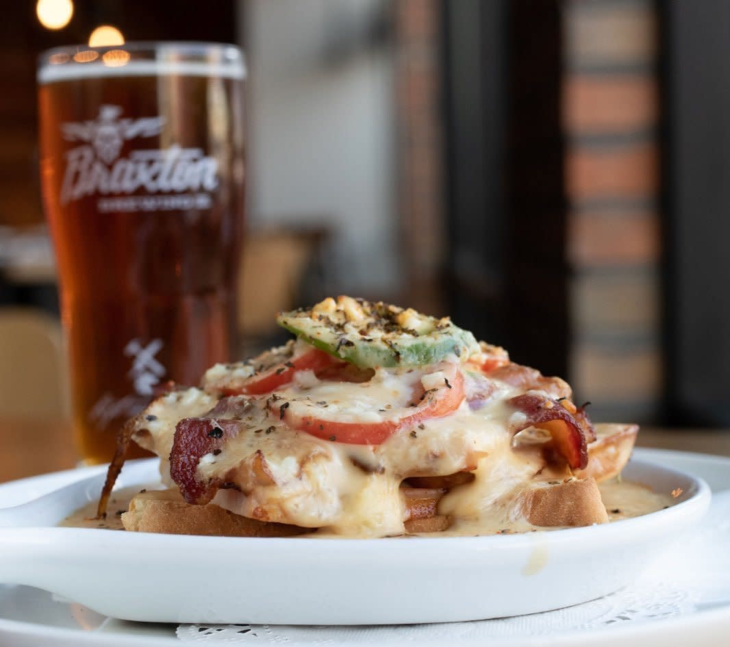A hot brown sandwich on a white plate with a glass of Braxton craft beer at Parlor on Seventh restaurant