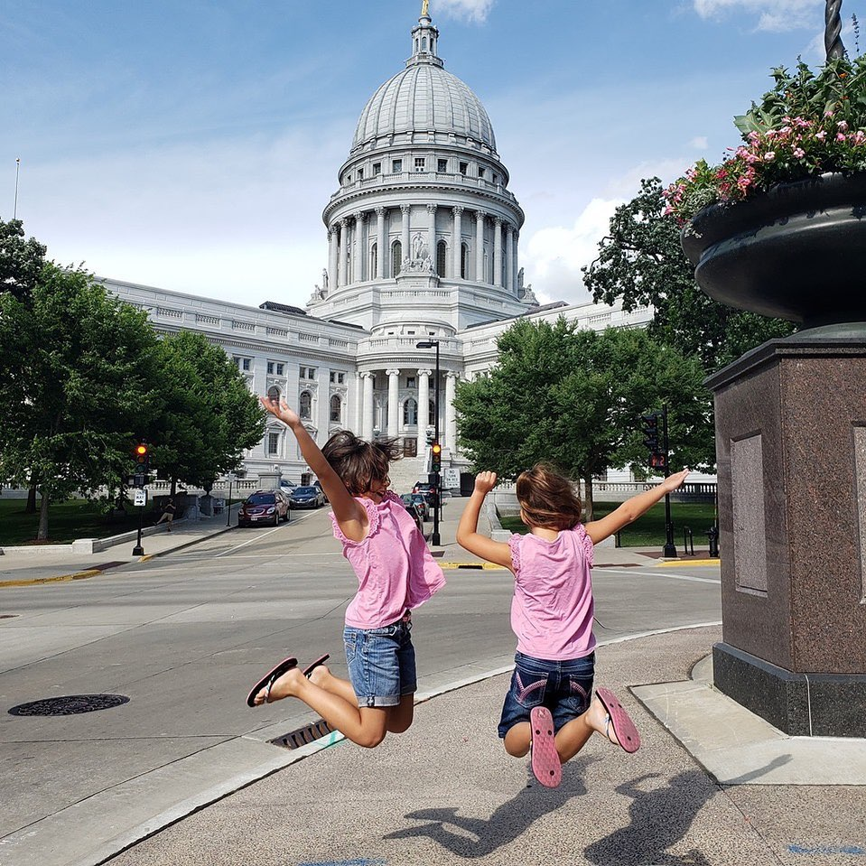 Two children jumping in the air with the Wisconsin State Capitol in the background