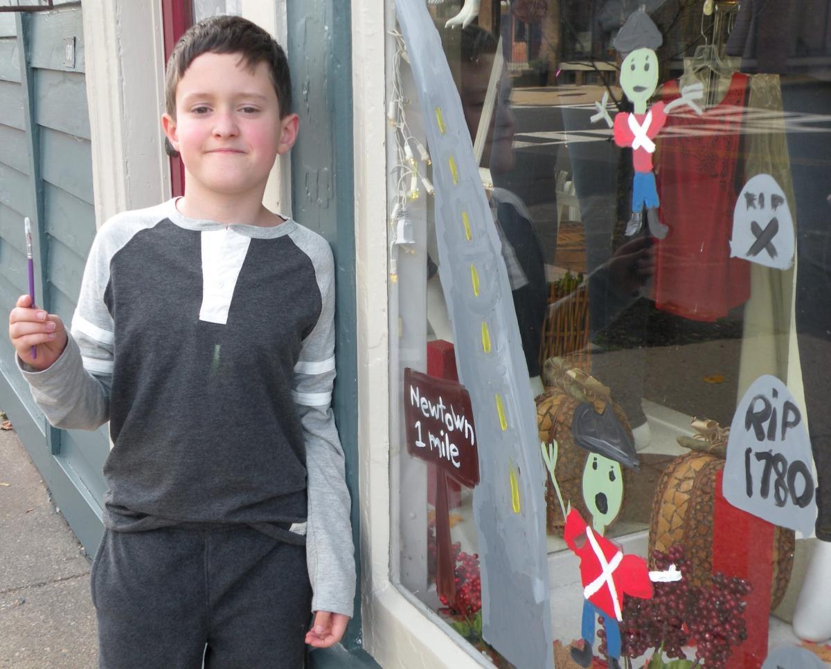 Little boy painting Newtown window