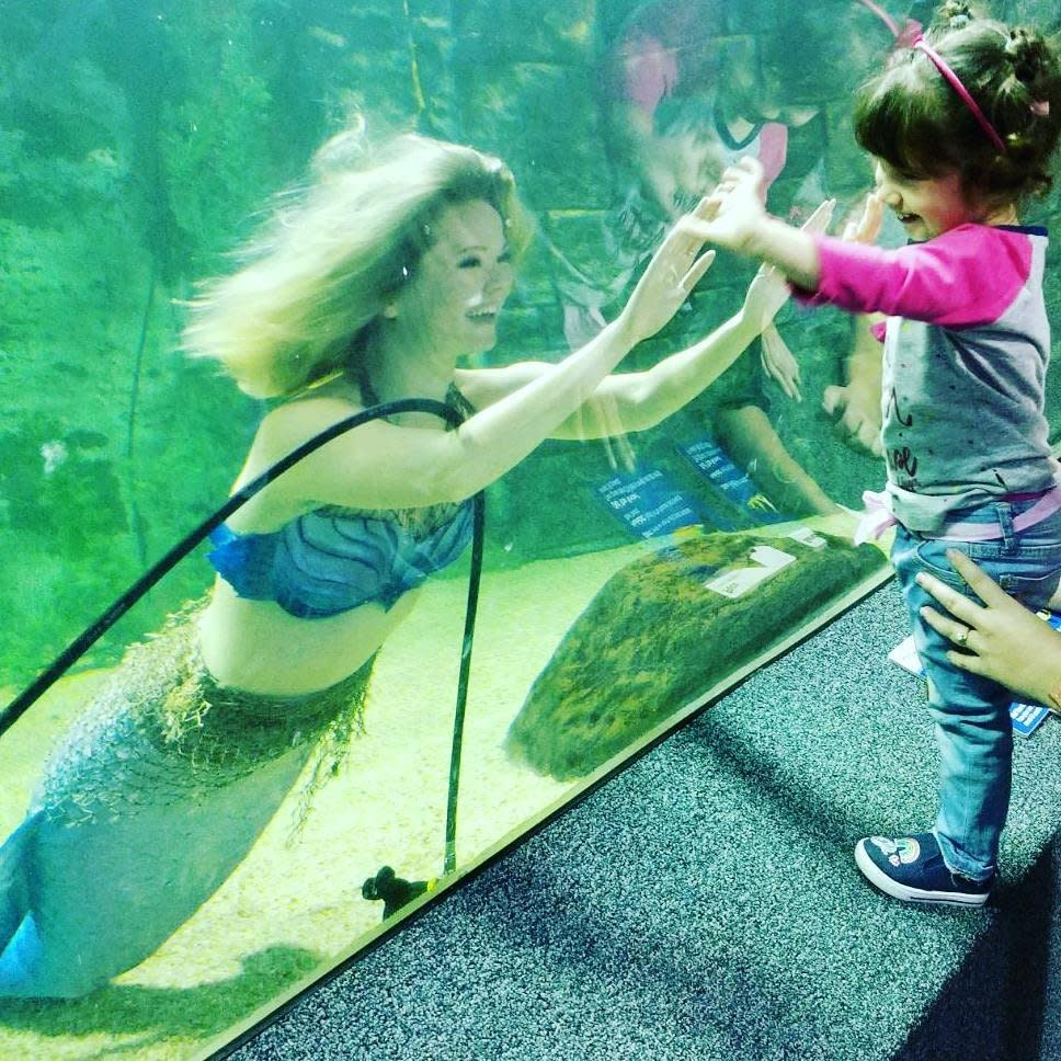 A little girl in a pink shirt reaching her hands up to a Newport Aquarium wall to match the hands of a mermaid swimming in the water