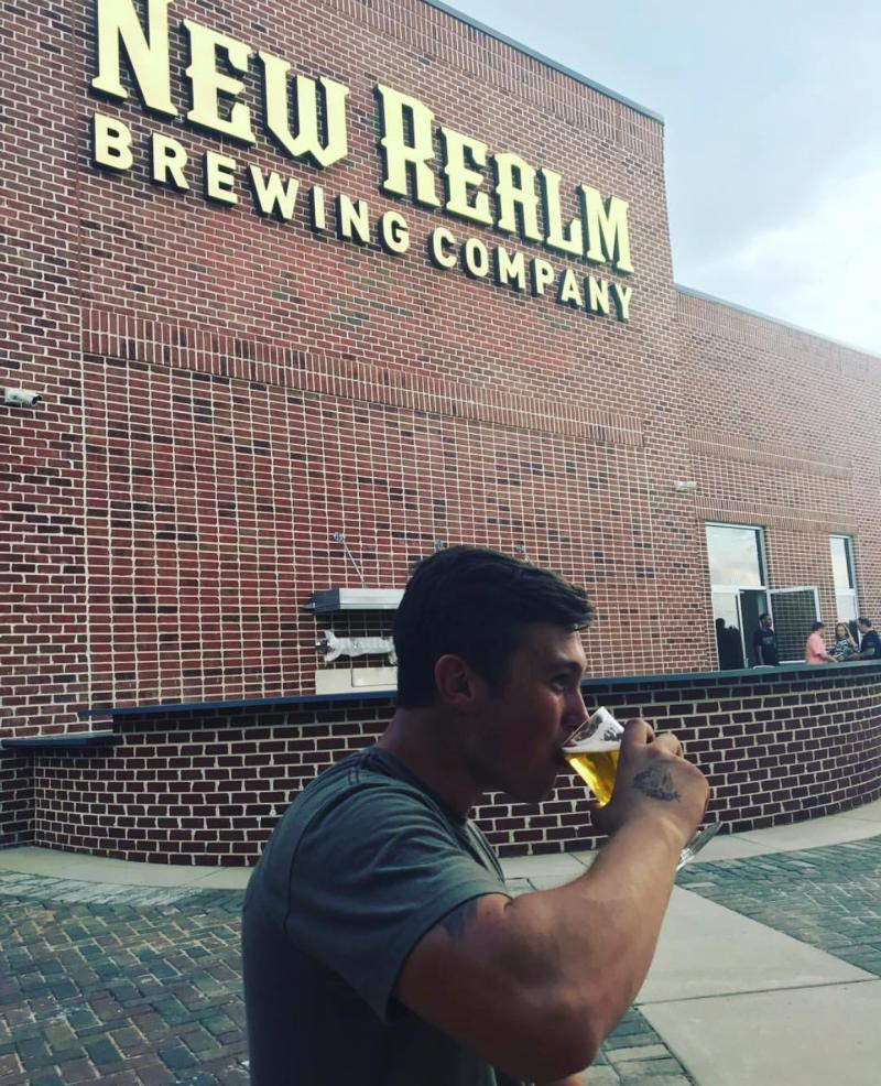 A patron sips a glass of brew in front of the New Realm Brewing signage.