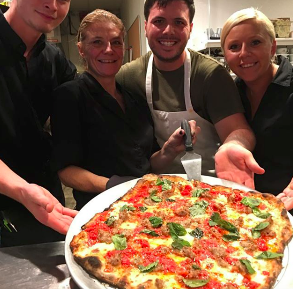 Smiling chefs presenting a pizza at Marcello's Coal Fired Pizza in Bordentown, NJ