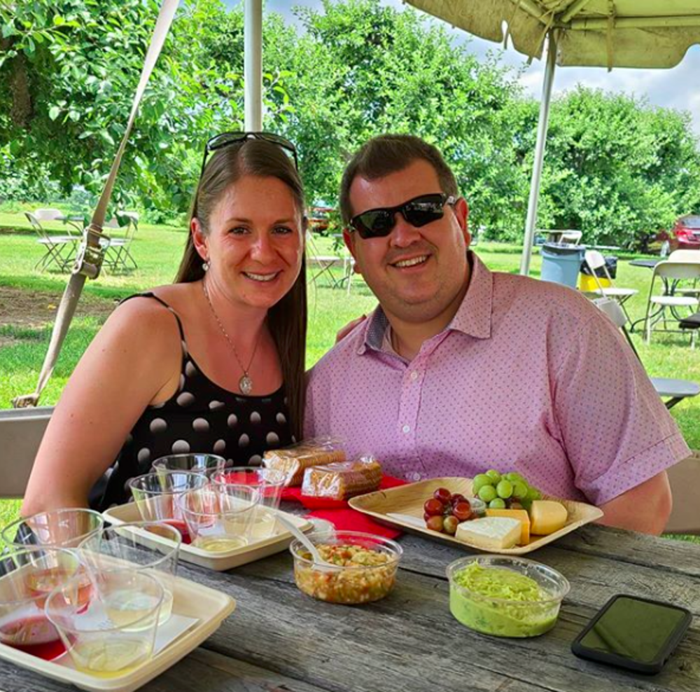 A smiling couple enjoying the Winery Weekend Music Series at Terhune orchards in Princeton, NJ.