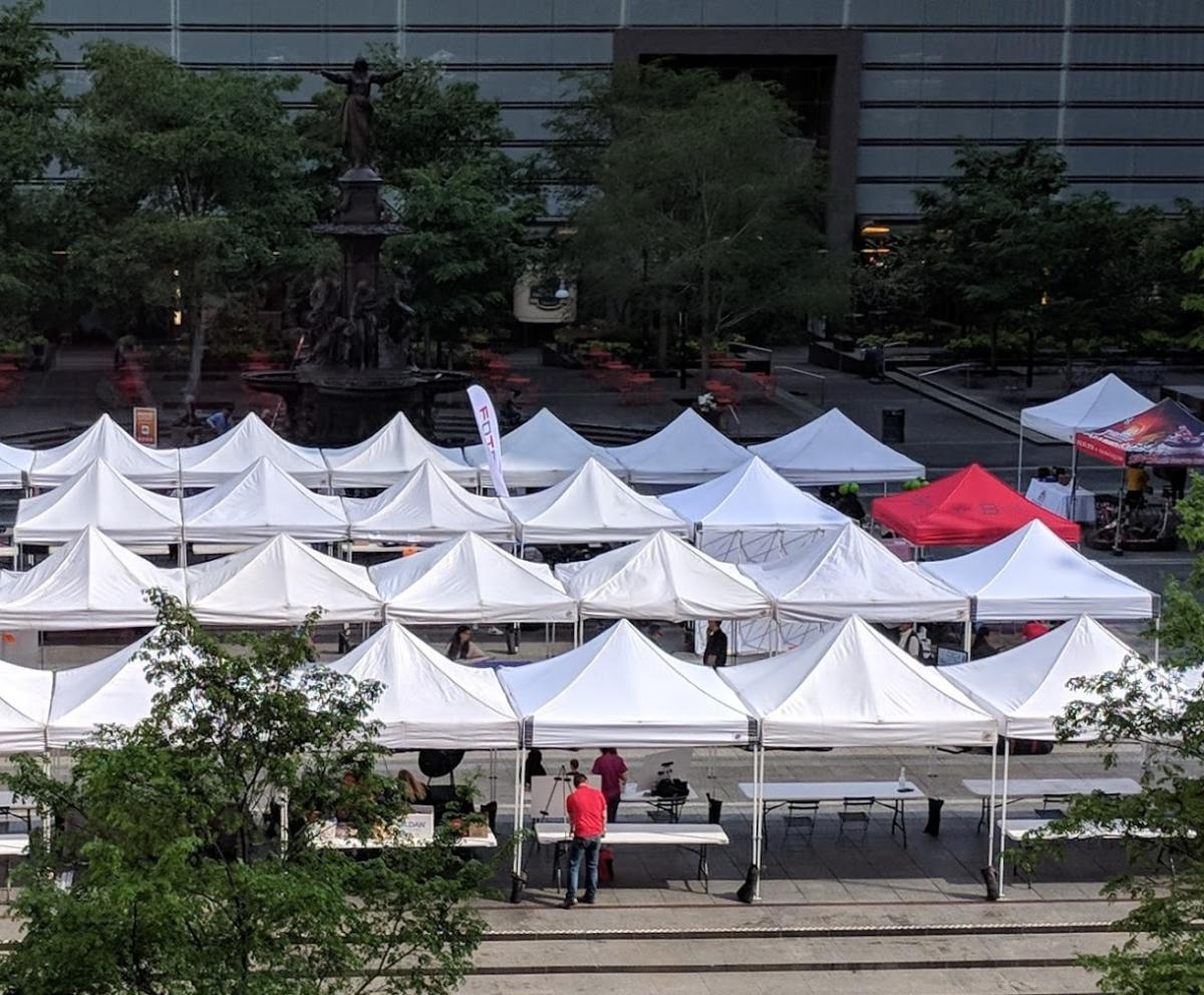 """Rows of white tents on Fountain Square in Cincinnati with one red tent that reads """"The B-Line"""" in blue lettering"""