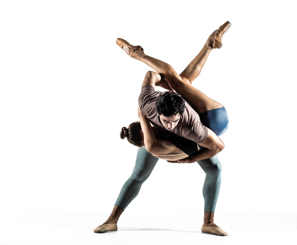 A man and woman performing an acrobatic dance in front of a white background.