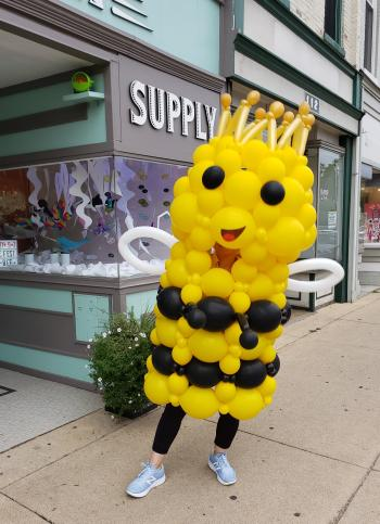 A person wears the Queen Bizzy Bee costume, a yellow and black balloon sculpture of a smiling queen honeybee.