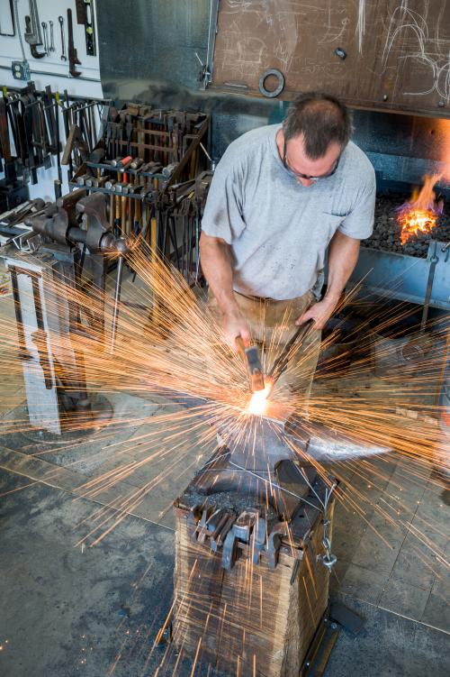 A metal worker forges his craft in Asheville.
