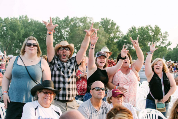 People with their arms up in excitement at Country Jam