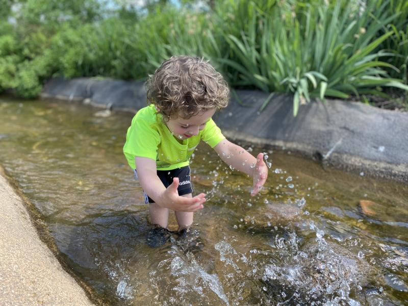 Little boy playing in River Prairie Park stream