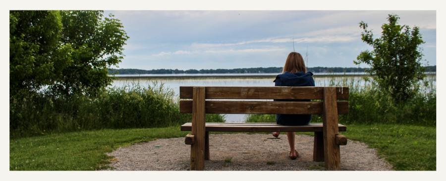 Woman sitting on bench overlooking Rock Lake at Knorth Park in Lake Mills, WI