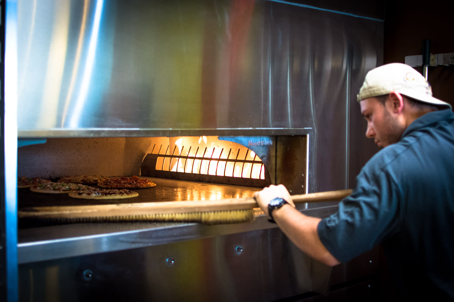 Employee making oven-fired pizzas at Pizza Artista in Lafayette, LA