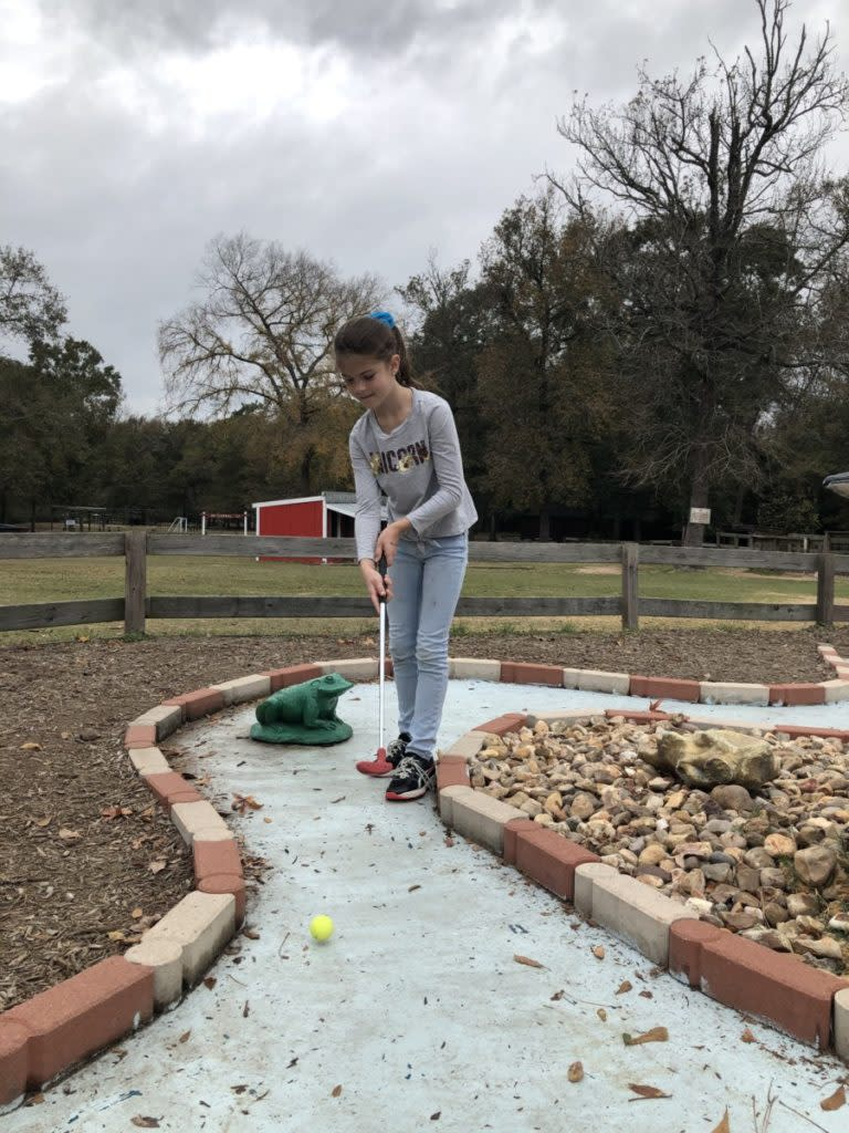 a girl Mini Golfing at 7 acre Wood