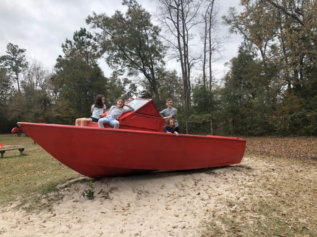 3 kids sit on a red boat that is beached at 7 acre Wood in Conroe Texas