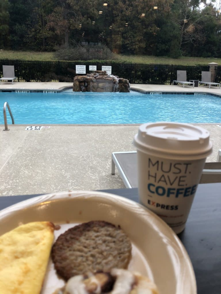 A plate of Breakfast and coffee with the view of a pool at Holiday Inn and Suites in Conroe, Texas