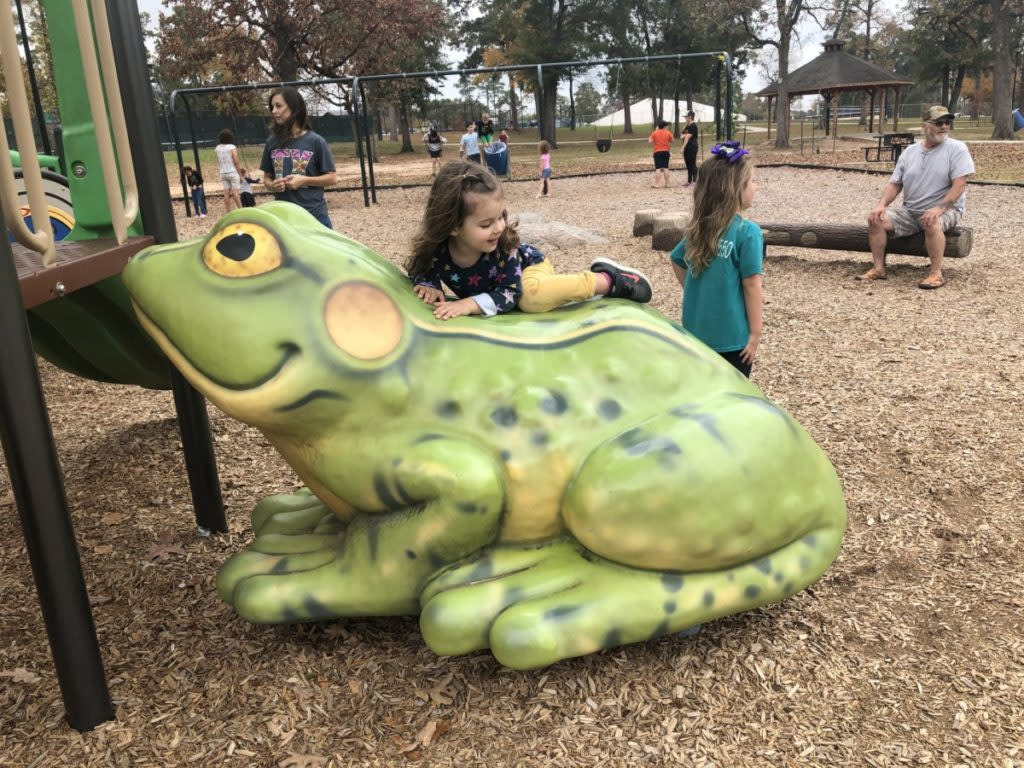 A toddler climbs a frog at Candy Cane Park in Conroe Texas