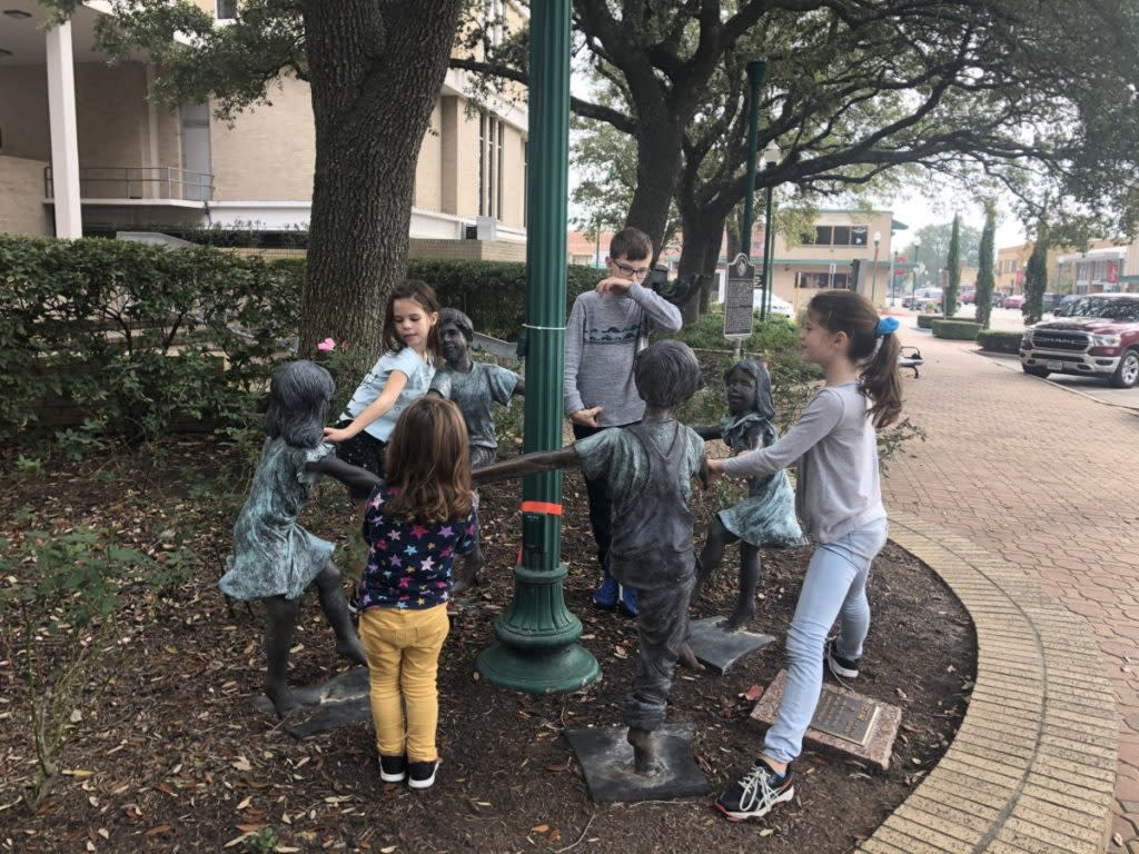 4 kids playing with a statue Ring-around-the Roses in Downtown Conroe, Texas