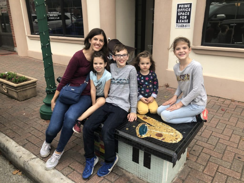 Mom and 4 kids sitting on a tiled Art bench in Downtown Conroe Texas