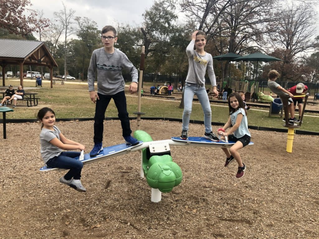 4 kids play on the Playground dragonfly at Candy Cane Park in Conroe, Texas