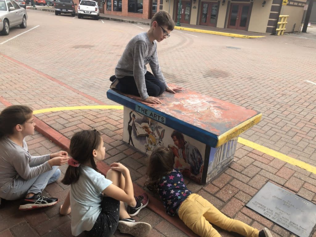 4 kids admire the ARTS bench in downtown Conroe