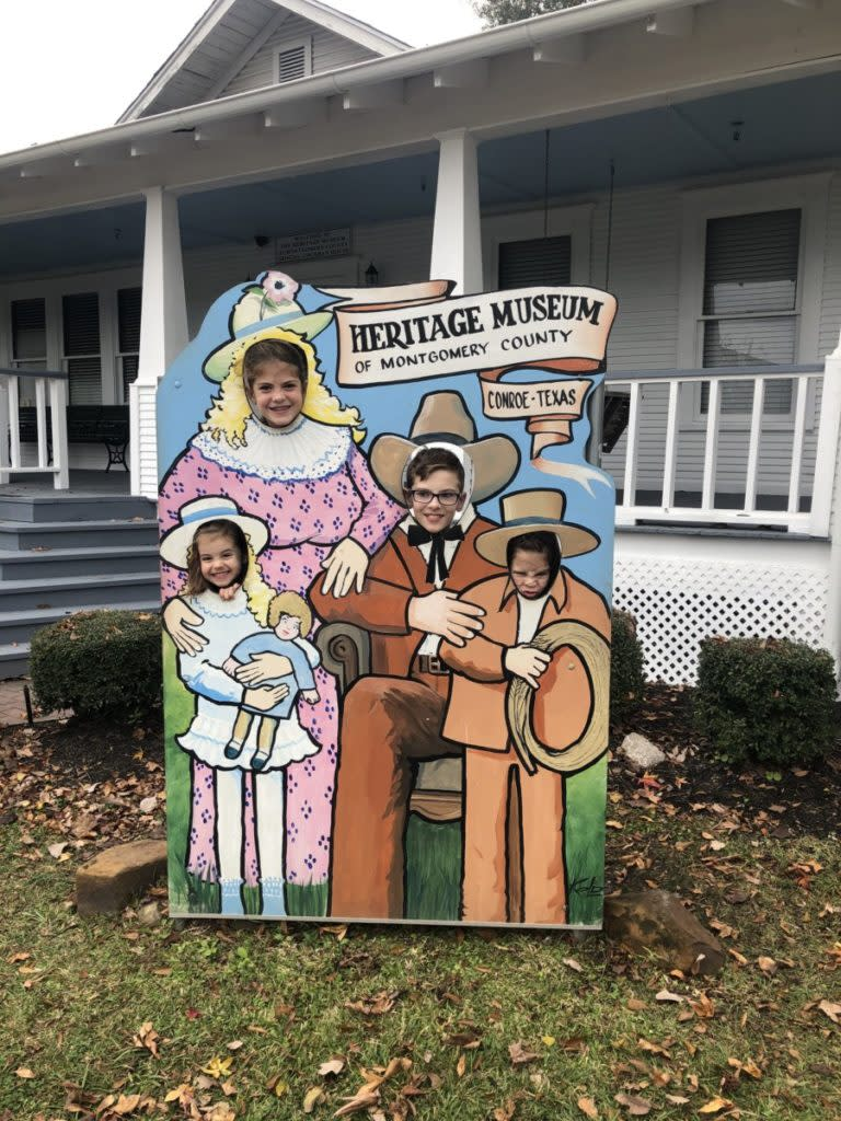 4 kids pose behind a photo opp at Heritage Museum of Montgomery County in Conroe Texas