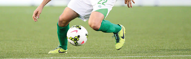 Man's feet kicking a soccer ball of the Energy FC