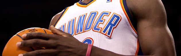 Man holding basketball in a Thunder uniform