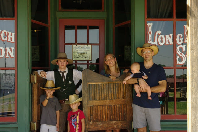 Family of 5 standing outside of an old fashioned saloon