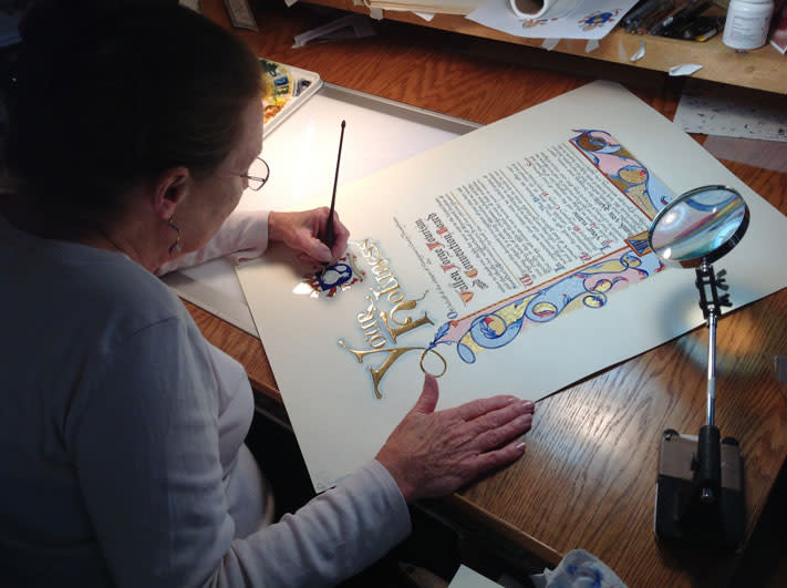 Rosemary Buczek works on the scroll that will be delivered to Pope Francis.