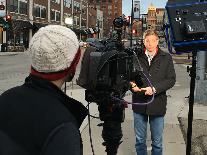 Reporter standing doing a live shot on a street corner in Des Moines