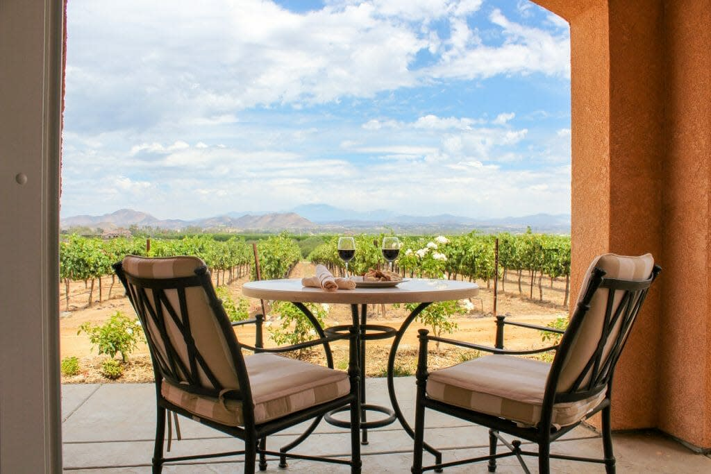 Two chairs and bistro table on terrace overlooking the vineyards in Temecula