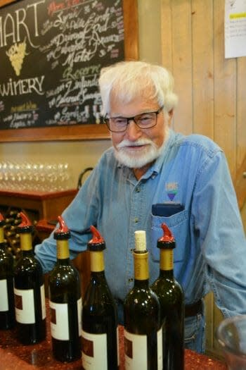 White haired man with beard, Joe Hart from Hart Family Winery Temecula, standing behind bar with wine bottles in front of him