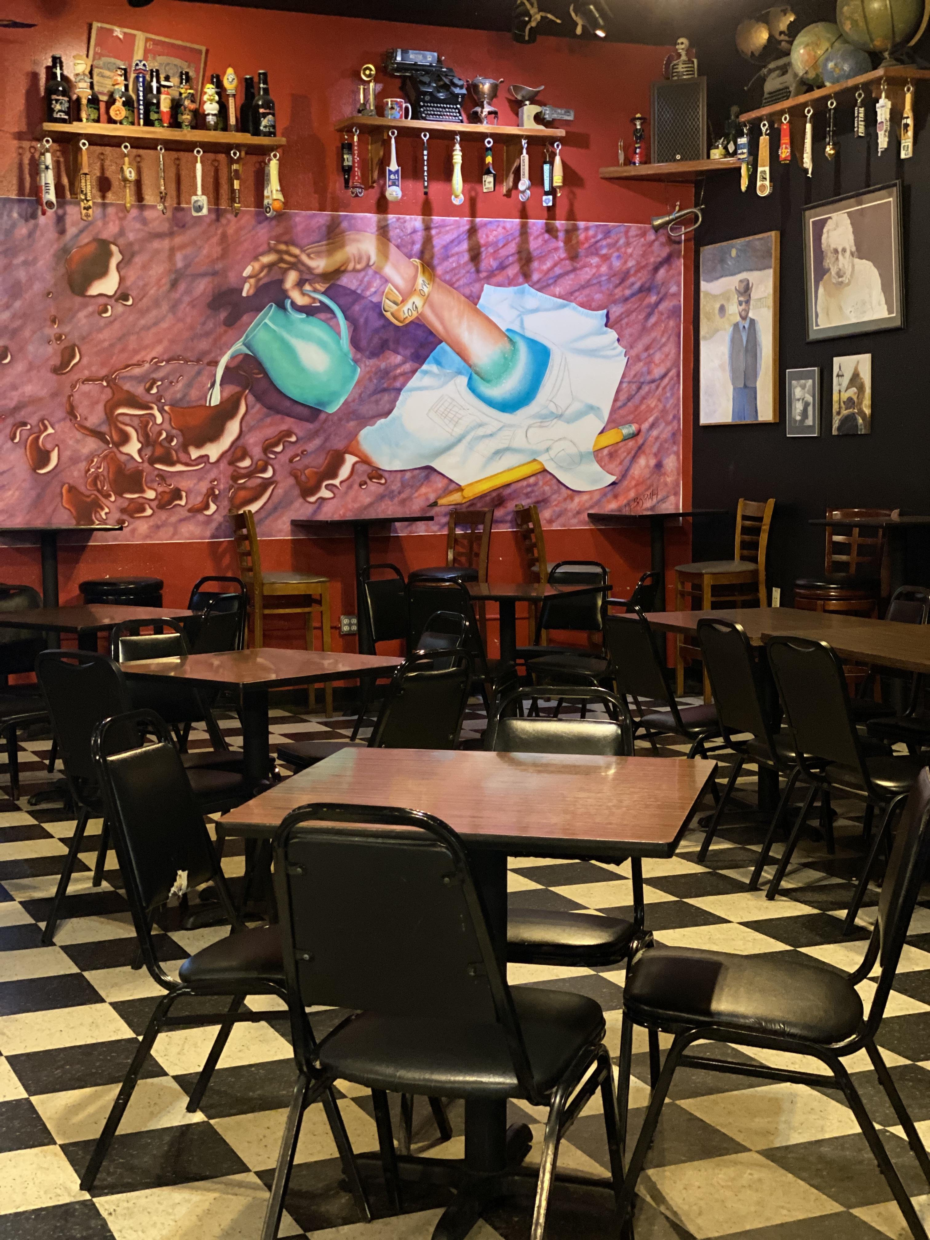 dining area of Logon Cafe with mural of hand pouring wine from pitcher