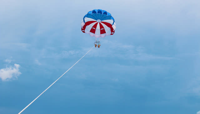 View from the boat of a couple parasailing