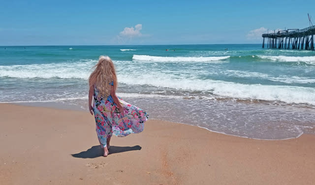 A woman walks on the beach toward the water in the Outer Banks