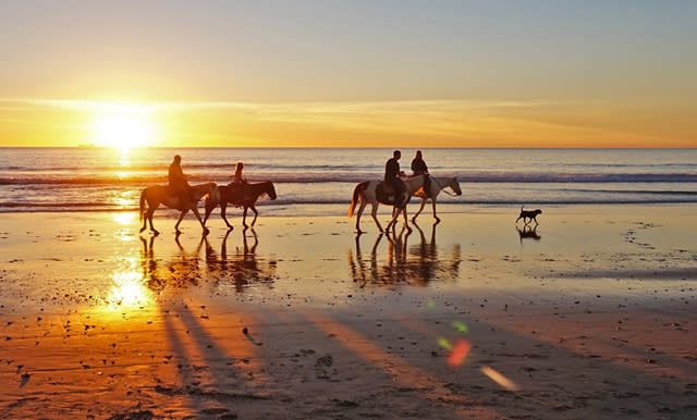 Riding horseback on the beach at sunset in the Outer Banks