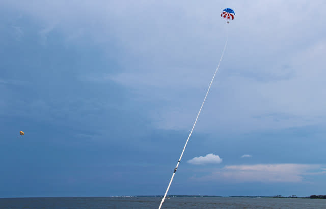 View from the boat of a couple parasailing in the Outer Banks