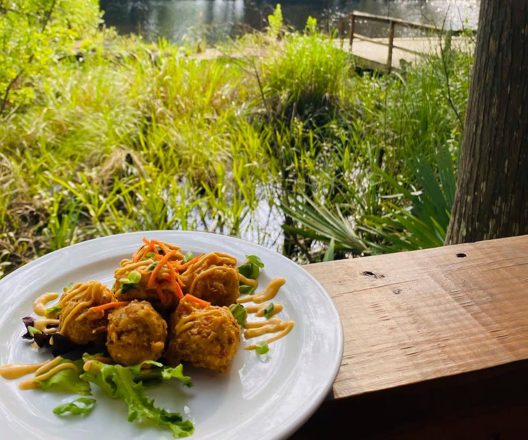 Crawfish beignets served on a plate that sits on a table overlooking a bayou